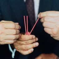 Three businessmen picking straws, focus on hands, close-up