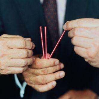 Three businessmen picking straws, focus on hands, close-up