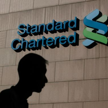 A  man walks pass the Standard Chartered Bank headquarters in Hong Kong Wednesday, Oct. 13, 2010. Standard Chartered PLC said Wednesday it is asking its shareholders for nearly 3.3 billion pounds ($5.2 billion) in a rights issue to satisfy tighter international capital requirements for banking.  (AP Photo/Kin Cheung)