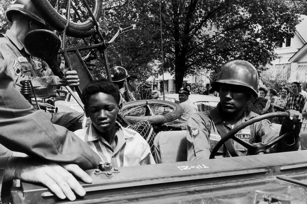 1957:  Caucasian National Guardsmen give an African-American student and his bicycle a lift to school while enforcing desegregation at Central High School in Little Rock, Arkansas. A cameraman and a crowd watch from the sidewalk.