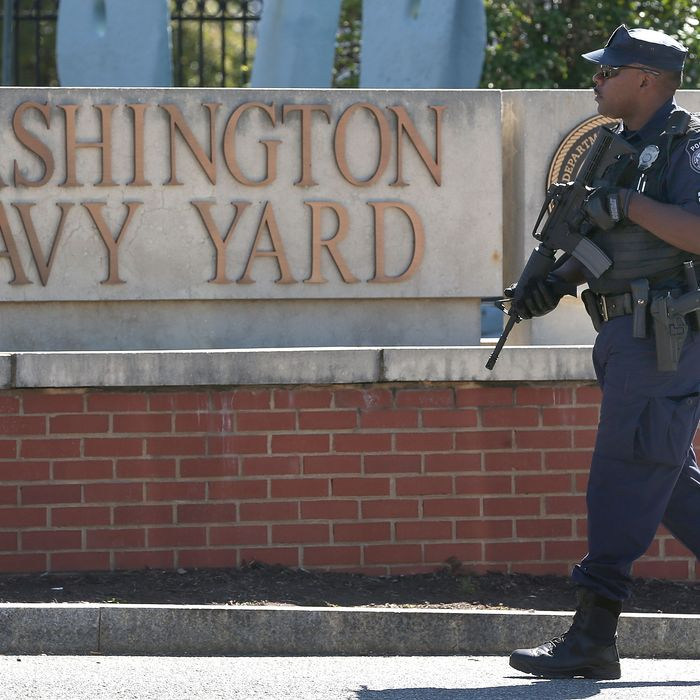 WASHINGTON, DC - SEPTEMBER 17: A police officer stands guard at the front gate of the Washington Naval Yard September 17, 2013 in Washington, DC. Yesterday a defense contractor named Aaron Alexis allegedly killed at least 13 people during a shooting rampage at the Navy Yard before being killed by police. (Photo by Mark Wilson/Getty Images)