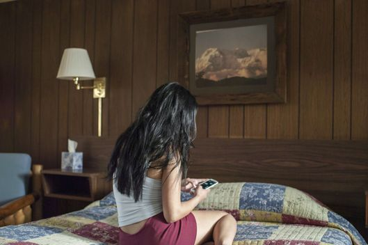 Young woman with mobile phone on hotel bed