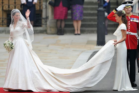 Kate in an Alexander McQueen dress by Sarah Burton, with her sister Pippa holding her train.