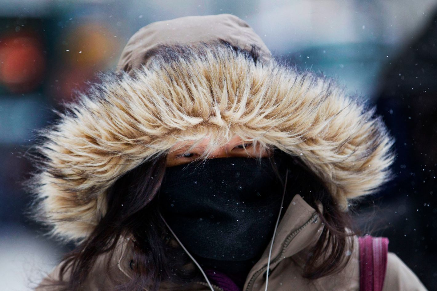 A pedestrian covers her face to keep warm in New York, U.S., on Friday, Jan. 3, 2014. Wind-driven snow whipped through New Yorks streets and piled up in Boston as a fast-moving storm brought near-blizzard conditions to parts of the Northeast, closing roads, grounding flights and shutting schools. Photographer: Jin Lee/Bloomberg via Getty Images