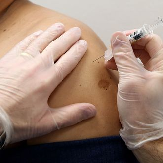 Fredy DeLeon (L) receives a flu shot from Walgreens pharmacist Robert Fox at a Walgreens Pharmacy on January 14, 2014 in Concord, California. Public health officials are encouraging residents to get flu shots as an aggressive strain of the H1N1