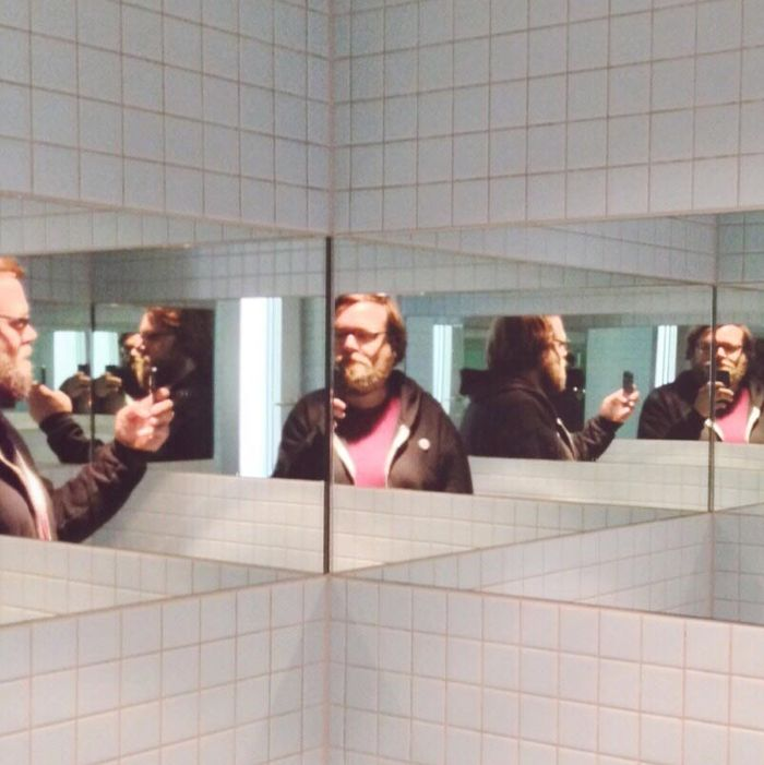 Multiple Reflection Of Man Taking Self Portrait Through Phone In Restroom