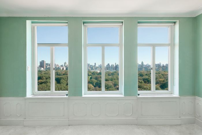 A room with three windows overlooking trees and skyline with tall buildings.