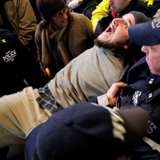 An Occupy Wall Street protester yells as he is arrested by the police after blocking an intersection near The New York Stock Exchange in New York, Thursday, Nov. 17, 2011.   Two days after the encampment that sparked the global Occupy protest movement was cleared by authorities, demonstrators marched through New York's financial district  and promised a national day of action with mass gatherings in other cities.   (AP Photo/Seth Wenig)