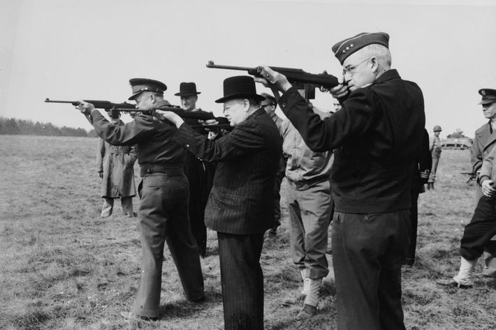 1944: From left to right: American General Dwight D Eisenhower (1890 - 1969, later the 34th President of the United States), British Prime Minister Winston Churchill (1874 - 1965) and Lt-Gen Omar Bradley (1893-1981), shooting with the American Army's new carbine at an American armoured troops camp in England. The Allied war chiefs are escorting the British prime minister on a tour of inspection. (Photo by Keystone/Getty Images)
