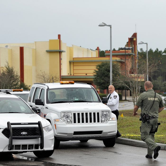 A Pasco County sheriff's deputy, right, and an independent security guard block the driveway to the Cobb theater Tuesday, Jan. 14, 2014, in Wesley Chapel , Fla. A 71-year old retired Tampa, Fla., police officer is charged with second degree murder after shooting Chad Oulson Monday during a cell phone dispute inside the theater. Oulson's wife Nicole, was also shot while trying to protect her husband. (AP Photo/Chris O'Meara)