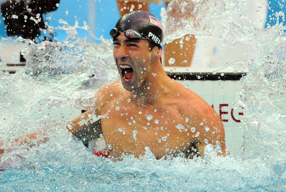 US swimmer Michael Phelps reacts after winning the men's 100m butterfly swimming final at the National Aquatics Center during the 2008 Beijing Olympic Games in Beijing on August 16, 2008.  Phelps won the Olympic Games men's 100m butterfly gold medal here. The victory gave him a seventh gold medal here and equalled Mark Spitz's 1972 record.   AFP PHOTO / MARTIN BUREAU (Photo credit should read MARTIN BUREAU/AFP/Getty Images)