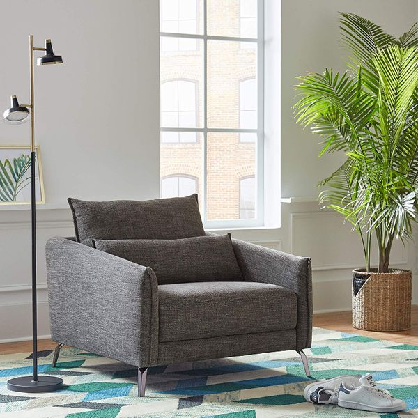 A black Wayfair floorlamp with a brass top leading to two black and brass lights next to a grey chair, a grey and blue patterned rug, and a potted plant . The Strategist - Very Tasteful Lamps from Amazon's Rivet and Stone and Beam Are on Sale