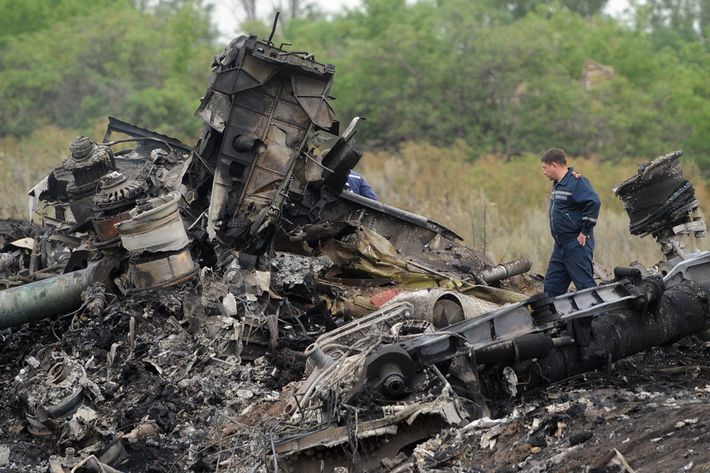 Rescuers stand on July 18, 2014 on the site of the crash of a Malaysian airliner carrying 298 people from Amsterdam to Kuala Lumpur, near the town of Shaktarsk, in rebel-held east Ukraine. Pro-Russian separatists in the region and officials in Kiev blamed each other for the crash, after the plane was apparently hit by a surface-to-air missile. All 298 people on board Flight MH17 died when the plane crashed. Rescue workers at the crash site said that they had found one of the black boxes from the passenger liner. AFP PHOTO/DOMINIQUE FAGET        (Photo credit should read DOMINIQUE FAGET/AFP/Getty Images)
