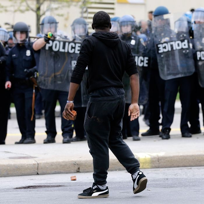 A demonstrator walks past police with a brick as they respond to thrown objects, Monday, April 27, 2015, after the funeral of Freddie Gray in Baltimore.