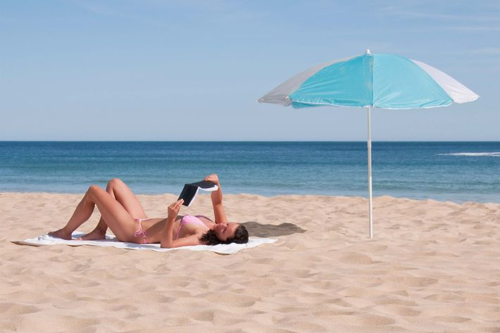 Portugal, Lagos, Mid adult woman reading book on beach