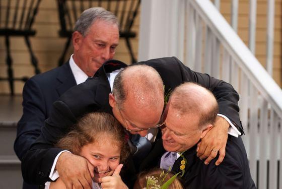 New York City Mayor Michael Bloomberg (back) watches while Jonathan Mintz (2nd L), the city's consumer affairs commissioner, John Feinblatt  (R), a chief adviser to the mayor, along with their  daughters Maeve (L) and Georgia do a group hug at Gracie Mansion in New York July 24, 2011. Hundreds of gay and lesbian New Yorkers were married this weekend, as the Empire State becomes the sixth state in the U.S. to embrace same-sex marriage. AFP PHOTO/DON EMMERT (Photo credit should read DON EMMERT/AFP/Getty Images)
