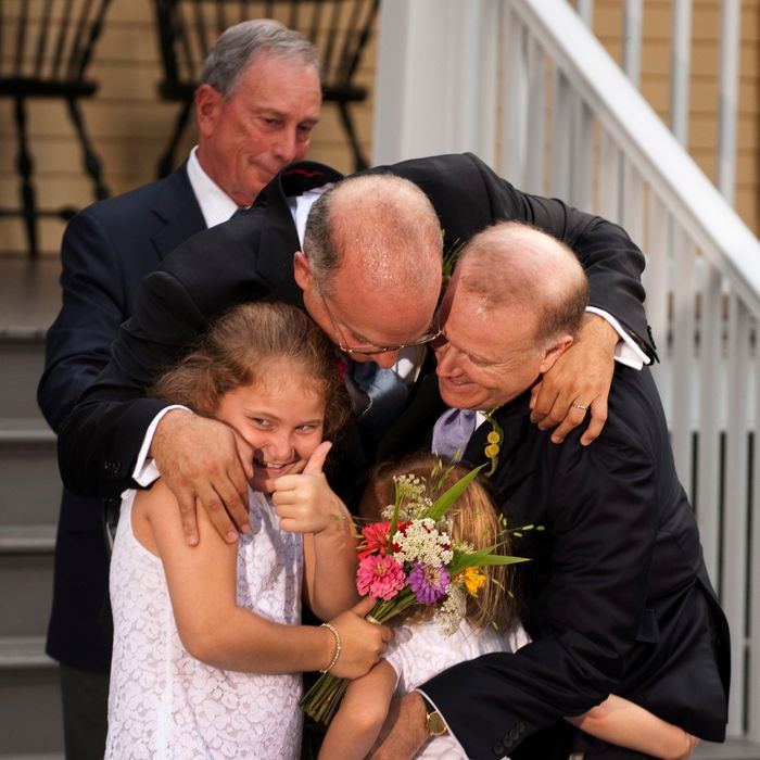 New York City Mayor Michael Bloomberg (back) watches while Jonathan Mintz (2nd L), the city's consumer affairs commissioner, John Feinblatt (R), a chief adviser to the mayor, along with their daughters Maeve (L) and Georgia do a group hug at Gracie Mansion in New York July 24, 2011. Hundreds of gay and lesbian New Yorkers were married this weekend, as the Empire State becomes the sixth state in the U.S. to embrace same-sex marriage.