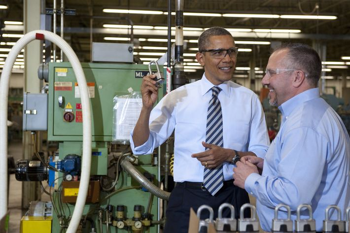 US President Barack Obama holds up a lock as he tours the manufacturing facility at Master Lock, maker of security locks, alongside Bob Rice (R), Master Lock Senior Vice President, prior to speaking on the economy in Milwaukee, Wisconsin, on February 15, 2012.
