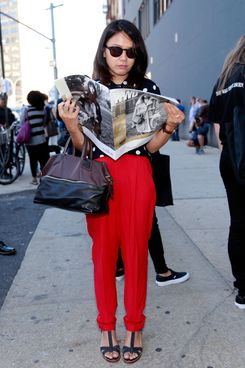 A showgoer reading WWD at Fashion Week.