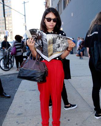 A showgoer reading WWD at Fashion Week.