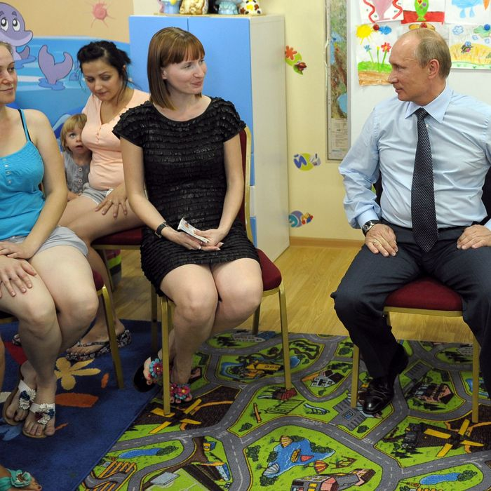 Russian President Vladimir Putin (L) attends a meeting with women who has suffered from the flood in southern Russian town of Gelendzhik on July 25, 2012, visiting the region.