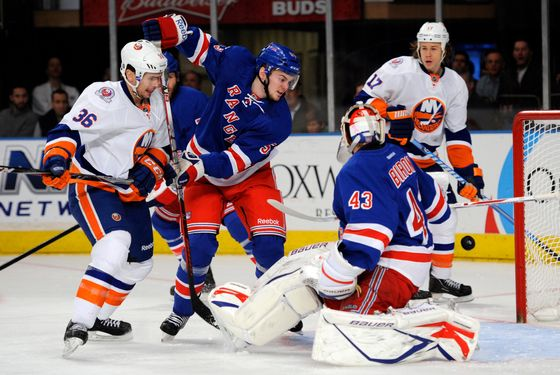 New York Rangers goalie Martin Biron, right, reaches back to make a save on a shot by New York Islanders' Tim Wallace (36) while Rangers' Tim Erixon (53) defends in the first period of an NHL hockey game in New York, Thursday, Dec. 22, 2011. (AP Photo/Henny Ray Abrams)