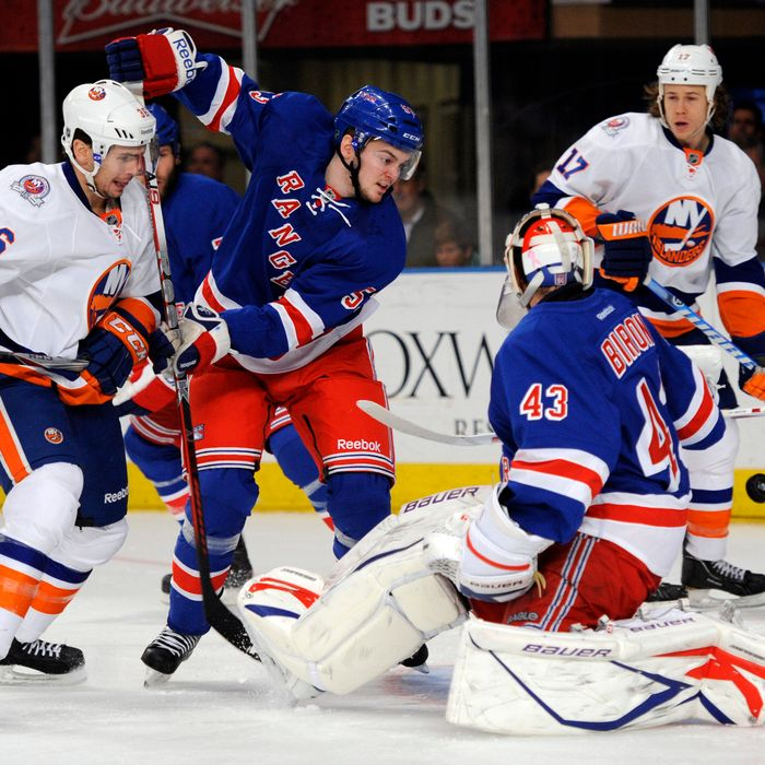 New York Rangers goalie Martin Biron, right, reaches back to make a save on a shot by New York Islanders' Tim Wallace (36) while Rangers' Tim Erixon (53) defends in the first period of an NHL hockey game in New York, Thursday, Dec. 22, 2011.