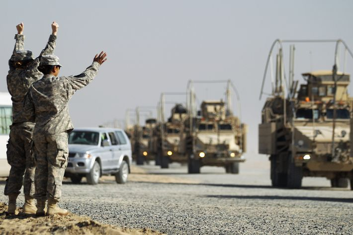 CAMP VIRGINIA, KUWAIT - DECEMBER 18: Soldiers wave to colleagues as a section of the last American military convoy to depart Iraq from the 3rd Brigade, 1st Cavalry Division arrives after crossing over the border into Kuwait on December 18, 2011 in Camp Virginia, Kuwait. Around 500 troops from the 3rd Brigade, 1st Cavalry Division ended their presence on Camp Adder, the last remaining American base, and departed in the final American military convoy out of Iraq, arriving into Kuwait in the early morning hours of December 18, 2011. All U.S. troops were scheduled to have departed Iraq by December 31st, 2011. At least 4,485 U.S. military personnel died in service in Iraq. According to the Iraq Body Count, more than 100,000 Iraqi civilians have died from war-related violence.   (Photo by Mario Tama/Getty Images)