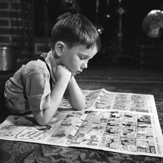 Boy reading funnies, indoors.