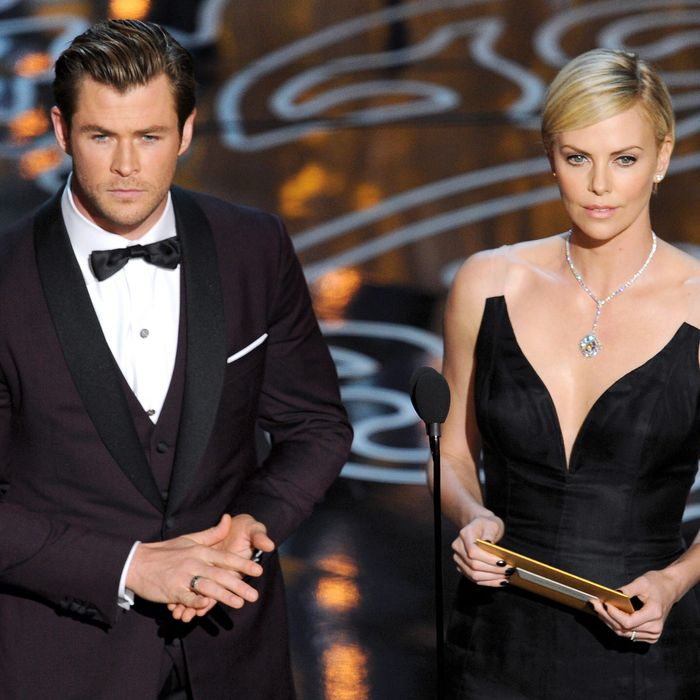 Actors Chris Hemsworth (L) and Charlize Theron speak onstage during the Oscars at the Dolby Theatre on March 2, 2014 in Hollywood, California.