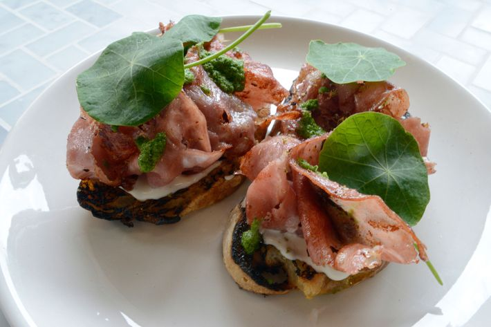 Griddled mortadella with whipped ricotta and a purée of sunflower seeds, lemon, and nasturtium leaves.
