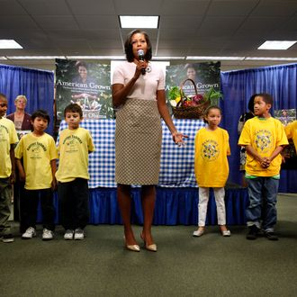 Surrounded by school children, First lady Michelle Obama speaks to a waiting crowd before signing copies of her book