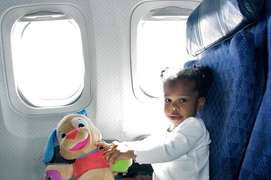 Baby girl playing with a toy in an airplane