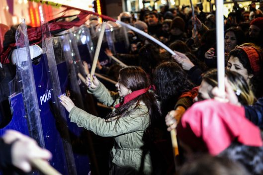 Turkish women beat riot police shields on March 8, 2015 as they try to cross a police cordon to reach Taksim square during a rally on Istiklal avenue in Istanbul to mark International Women's Day.  AFP PHOTO / BULENT KILIC        (Photo credit should read BULENT KILIC/AFP/Getty Images)