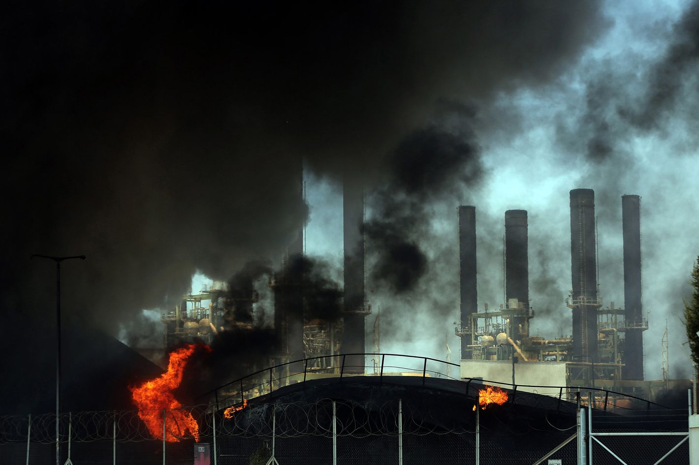 GAZA CITY, GAZA - JULY 29 :  The Gaza Strip's only power plant's fuel depot is seen engulfed in flames after it was hit by an Israeli air strike on July 29, 2014. The Gaza Strip's only power plant was forced to shut down Tuesday after an Israeli attack hit the facility's fuel depot. (Photo by Ali Jadallah/Anadolu Agency/Getty Images)