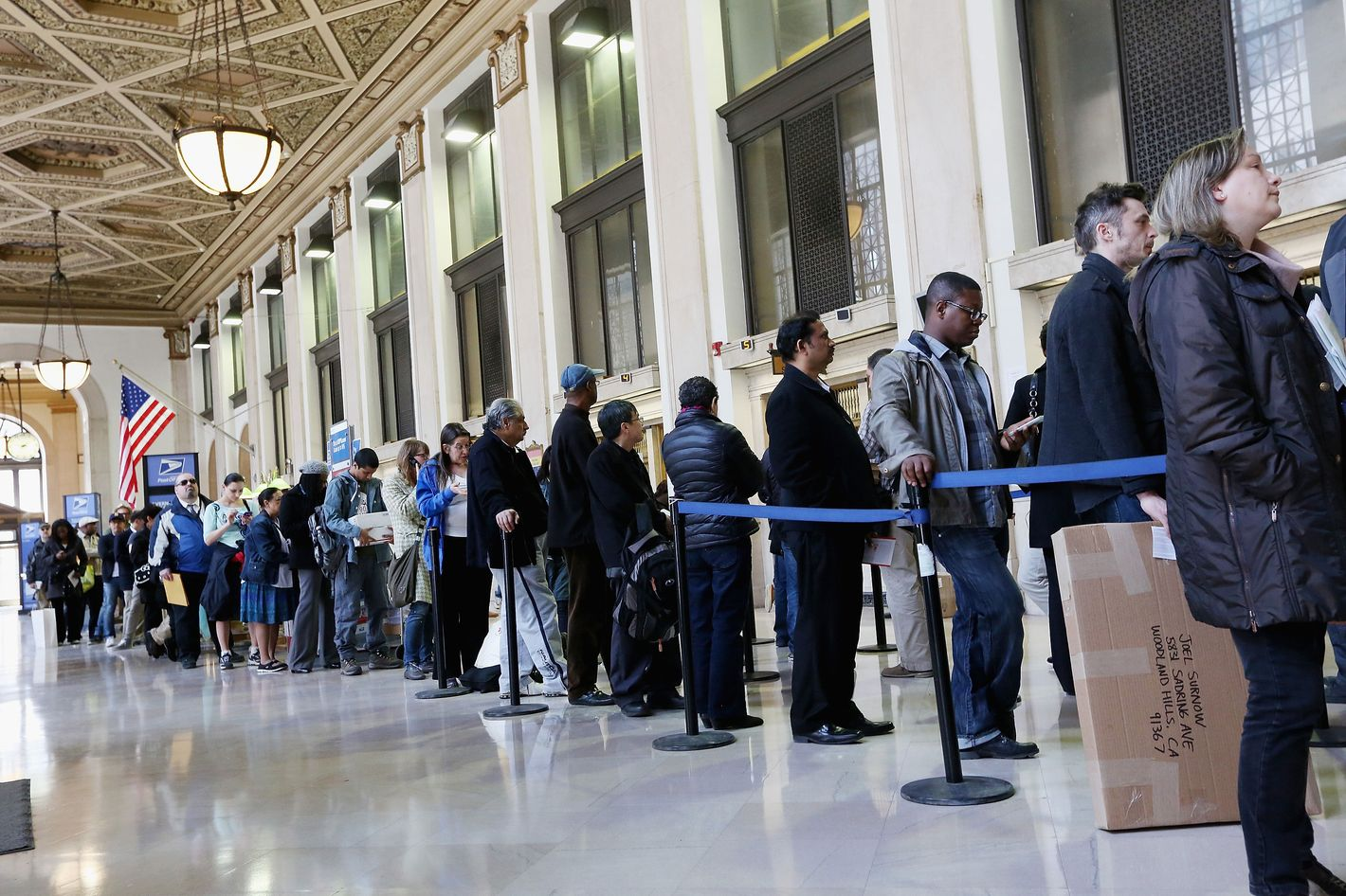 NEW YORK, NY - APRIL 15:  People wait in line inside the James A. Farley post office building April 15, 2013 in the Manhattan borough of New York City. With the U.S. tax deadline of midnight April 15 rapidly approaching, last-minute filers are filling up the nation's post offices.  (Photo by Mario Tama/Getty Images)