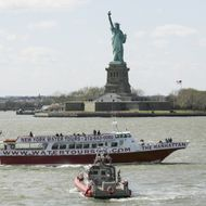 A tourist boat sails past the Statue of Liberty