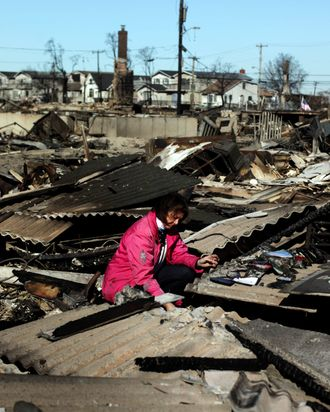 Kathy Lahey sifts through her damaged home for items to save November 4, 2012 in the Breezy Point neighborhood of the Queens borough of New York City. With the death toll currently over 100 and millions of homes and businesses without power, the US east coast is attempting to recover from the effects of floods, fires and power outages brought on by Superstorm Sandy.