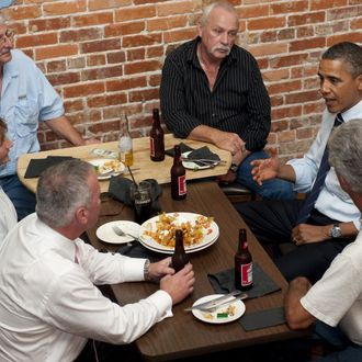 US President Barack Obama (2nd R) talks with unemployed construction workers over beer at the Harp and Celt Restaurant and Irish Pub in Orlando, Florida, October 11, 2011.
