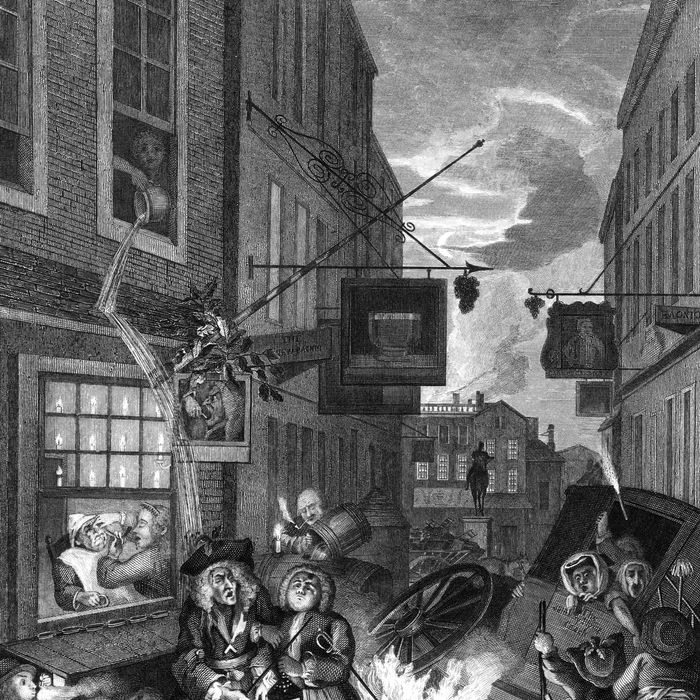 A busy London street at nighttime, 1738. The Salisbury Flying Coach lies overturned in the middle of the street, while homeless people huddle in a shelter and a figure in a window above empties a chamberpot over two passers-by. Engraved by W. Radclyffe from the original, 'Four Times of the Day - Night', by William Hogarth.