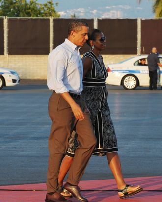 US President Barack Obama and First Lady Michelle Obama make their way to board Air Force One January 2, 2011 at Hickam Air Force Base in Honolulu.