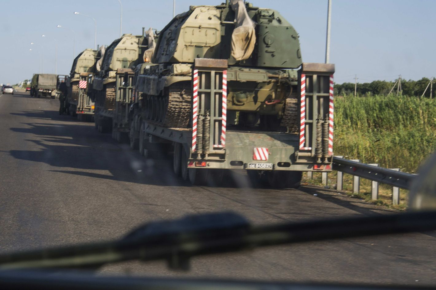 Column of tractors, self-propelled artillery transporting on the highway M 29 in the area of village Kursavka, Stavropol Krai, Russia. Each gun weighs 57 tons. According to the Russian soldiers are heading towards the Russian-Ukrainian border. Accompanied by armored vehicles just one driver.