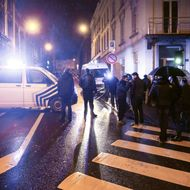 Journalists and residents stand near police vehicles as police set a large security perimeter in the city center of Verviers on January 15, 2015, during a