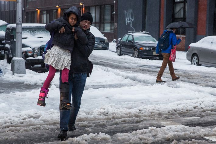 NEW YORK, NY - FEBRUARY 05:  A man carries a girl across a snowy street on February 5, 2014 in the Greenwich Village neighborhood of New York, United States. New York and surrounding regions were hit with yet another snow storm today, bringing snow and ice over night, and sleet and freezing rain during theday.  (Photo by Andrew Burton/Getty Images)