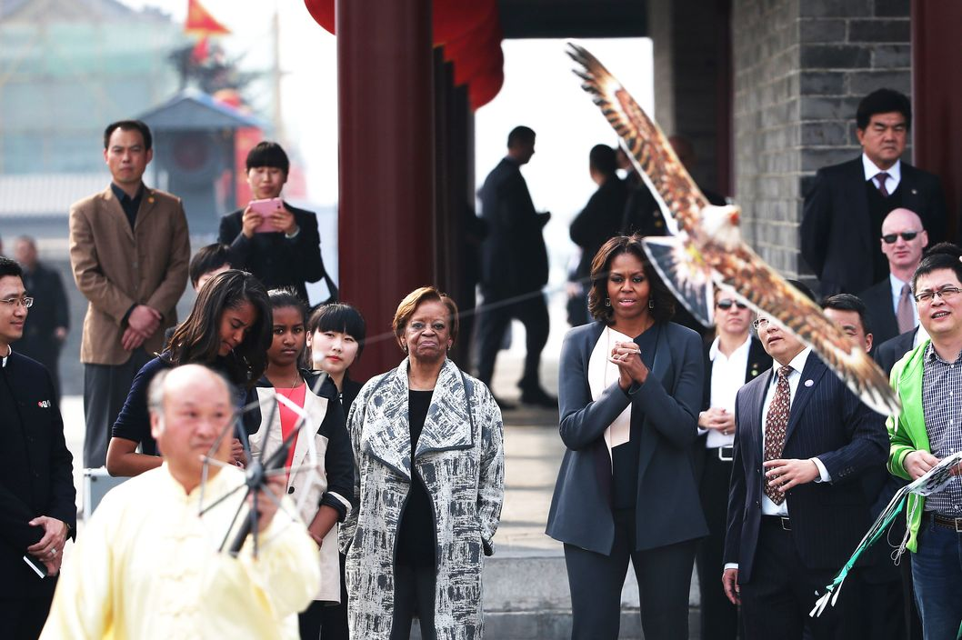 XI'AN, CHINA - MARCH 24:   First Lady Michelle Obama with her daughters Malia Obama and Sasha Obama, mother Marian Robinson watch a man flying a kite as they visit the Xi'an City Wall on March 24, 2014 in Xi'an, China. Michelle Obama's one-week-long visit in China will be focused on educational and cultural exchanges.  Michelle Obama's one-week-long visit in China will be focused on educational and cultural exchanges.  (Photo by Feng Li/Getty Images)