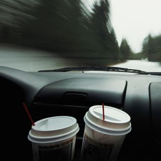 View through car windshield, focus on coffee cups (blurred motion)