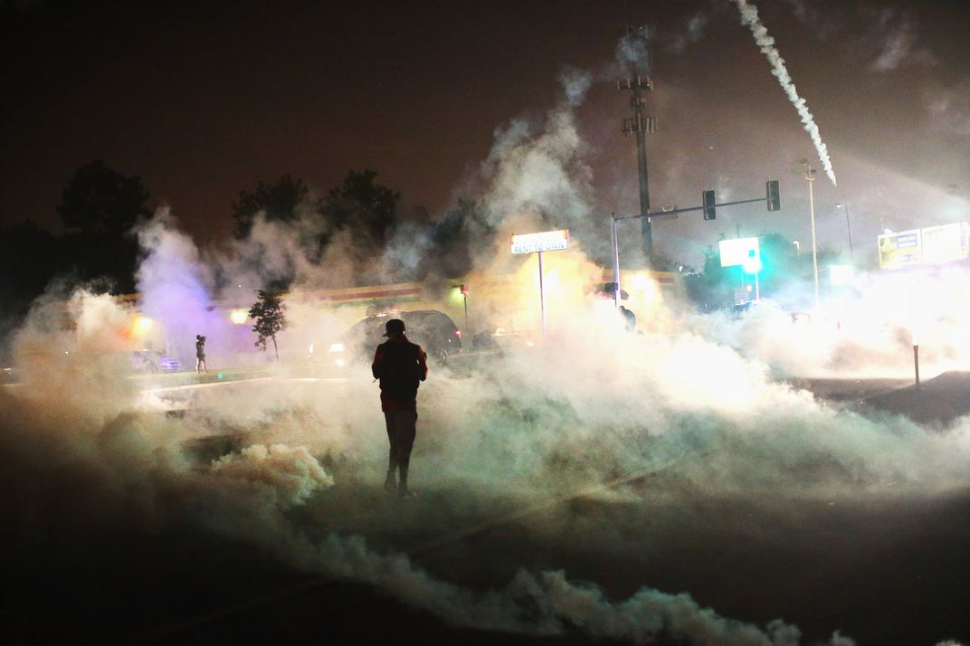 FERGUSON, MO - AUGUST 17:  Tear gas fills the street as a demonstrator walks through the haze during protests over the killing of teenager Michael Brown by a Ferguson police officer, on August 17, 2014 in Ferguson, Missouri. Despite the Brown family's continued call for peaceful demonstrations, violent protests have erupted nearly every night in Ferguson since his August 9, death.  (Photo by Scott Olson/Getty Images)