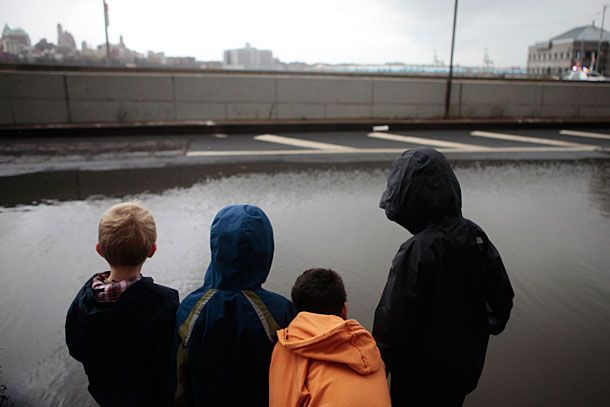 A group of kids look over receding floodwaters in lower Manhattan in New York, U.S., on Tuesday, Oct. 30, 2012. New York City officials began assessing damage after superstorm Sandy killed 10 people, sparked a fire that razed 80 homes in a Queens, flooded tunnels of the biggest U.S. transit system and left 750,000 customers without power, including the lower third of Manhattan. Photographer: Victor J. Blue/Bloomberg via Getty Images