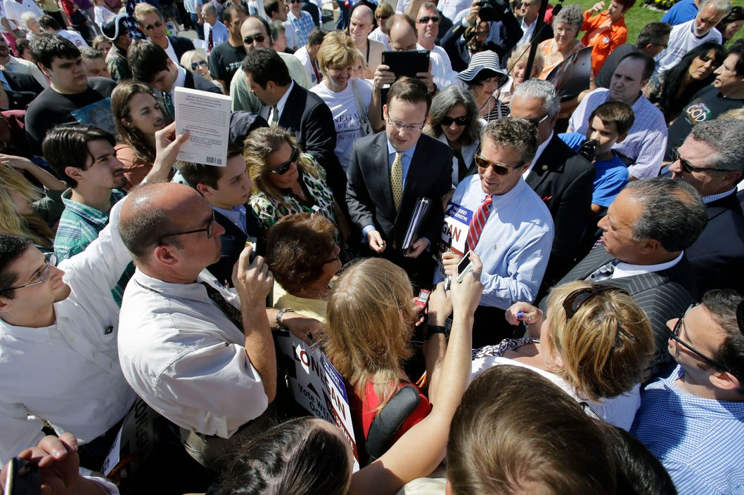 U.S. Sen. Rand Paul, R-Ky., center right in striped tie, is surrounded by supporters seeking autographs, at a rally in Clark, N.J., Friday, Sept. 13, 2013. Earlier, Paul told a crowd of about 200 that candidate for U.S. Senate in New Jersey, Steve Lonegan, will uphold the conservative libertarian principles they both share. Paul slammed Lonegan's Democratic challenger, Newark Mayor Cory Booker. (AP Photo/Mel Evans)
