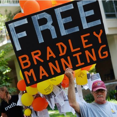 """A protestor holds a placard calling for the release for Pfc. Bradley Manning outside of Ft McNair on July 26, 2013 in Washington, DC. The trial of Manning, accused of """"aiding the enemy"""" by giving secret documents to WikiLeaks, is entering its final stage as both sides present closing arguments."""